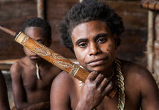 Korowai tribe woman smokes a traditional pipe. Tribe of Korowai Kombai , Kolufo. INDONESIA, ONNI VILLAGE, NEW GUINEA - JUNE 24: Korowai tribe woman smokes a Royalty Free Stock Images