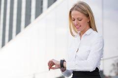 Korporacyjna biznesowa kobieta patrzeje zegarek i ono uśmiecha się fotografia stock