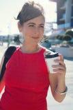 Korporacyjna kobieta w czerwieni sukni z takeaway kawą w ręce Fotografia Royalty Free