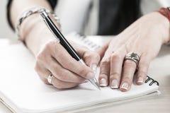 Korporacyjny biznes, kobiet ręki pisze w nutowym ochraniaczu zdjęcia royalty free