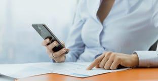 Korporacyjny bizneswoman u?ywa pieni??nych apps na jej smartphone obrazy stock