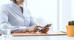 Korporacyjny bizneswomanu działanie i łączyć z jej smartphone obraz stock