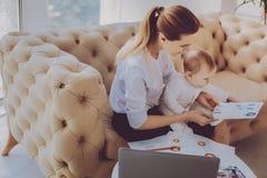 Korporacyjny daleki pracownika uczucie angażował w nowym projekcie podczas gdy pielęgnujący jej dziecka obraz royalty free