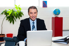 Korporacyjny lidera obsiadanie przed jego laptopem Obrazy Royalty Free