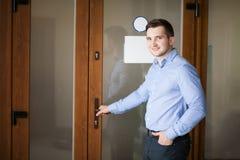 Korporacyjny mężczyzna otwiera jego biurowego drzwi zdjęcia stock