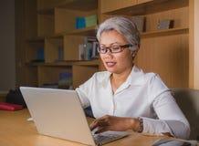 Korporacyjny portret atrakcyjna i szcz??liwa pomy?lna dojrza?a Azjatycka kobieta pracuje przy laptopu biurka ono u?miecha si? ufn zdjęcia royalty free