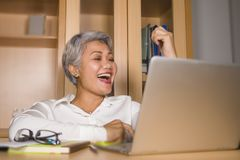 Korporacyjny portret atrakcyjna i szcz??liwa pomy?lna dojrza?a Azjatycka kobieta pracuje przy laptopu biurka ono u?miecha si? ufn obrazy stock