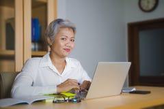 Korporacyjny portret atrakcyjna i szcz??liwa pomy?lna dojrza?a Azjatycka kobieta pracuje przy laptopu biurka ono u?miecha si? ufn obraz stock