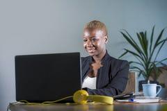 Korporacyjny portret młoda szczęśliwa i pomyślna czarna afro Amerykańska biznesowa kobieta pracuje przy nowożytnym biurowym uśmie zdjęcie stock
