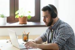 Korporacyjny pracownik ogląda stażowego wideo na jego laptopie oblicza fotografia stock