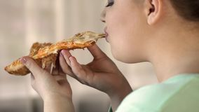 Korpulent kvinnlig äta pizzaskiva och tycka om smak, övervikt, skräpmat royaltyfria bilder