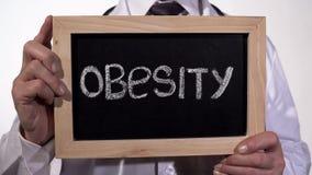 Korpulenz geschrieben auf Tafel in Doktorhände, gesunde Nahrungsempfehlungen stockfotografie