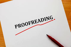 Korrekturläsa ord på det vita arket med den röda pennan Arkivfoto