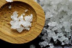 Korrels van zout op een houten lepel Stock Foto's