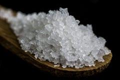 Korrels van zout op een houten lepel Stock Afbeelding