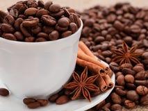 Korrels van zwarte koffie in een witte kop Kaneel en anijsplant op p Stock Foto's