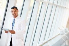 Korridor Doktor-Using Digital Tablet In des modernen Krankenhauses Lizenzfreie Stockfotos