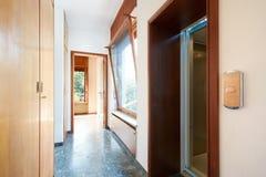 Korridor med den trägarderob-, fönster- och hissdörren i landshus royaltyfri bild