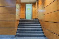 Korridor med granittrappa och den glass dörren royaltyfria bilder