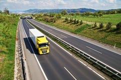 Korridorhuvudvägen med övergången för djurliv, huvudvägen går den gula lastbilen Arkivfoto