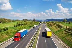 Korridorlandstraße mit dem Übergang für die Tiere, die Landstraßenfahrt gefärbt und die weißen LKWs lizenzfreies stockfoto