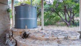 Korrugerad behållare för stålvattenlagring överst av stenhällmurverkstrukturen, med den lilla stenspringbrunnen framme fotografering för bildbyråer