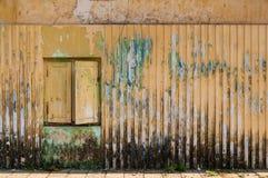 Korrugerad gul vägg med det stängde med fönsterluckor fönstret och flagande målarfärg arkivfoto