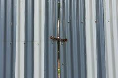 Korrugerad padlocked metallport Royaltyfri Bild