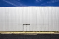 Korrugerad vägg för arkmetall med en dörr, gataskuggorna och blå himmel utomhus- Industriell blick digital bakgrund Royaltyfri Bild