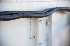 Korrugerade slangar med kabelkontakten på en metallyttersida arkivfoto