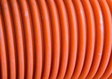 Korrugerat plast- rör av orange färg Fotografering för Bildbyråer