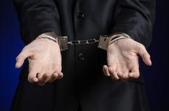 Korruption- och bestickningtema: affärsman i en svart dräkt med handbojor på hans händer på ett mörker - blå bakgrund i den isole royaltyfri bild