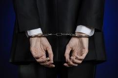 Korruption- och bestickningtema: affärsman i en svart dräkt med handbojor på hans händer på ett mörker - blå bakgrund i den isole arkivbild