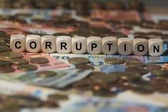 Korruption - Würfel mit Buchstaben, Geldsektorausdrücke - Zeichen mit hölzernen Würfeln Stockbild
