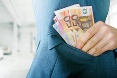 Korruptionskonzept, Hand, die Geld in Jackentasche einsetzt stockbild