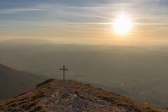 Kors överst av Mt Serrasanta Umbria, Italien, med varma guld- den timmefärger och solen som är låga på horisonten Royaltyfria Bilder