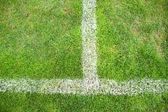 Kors av målade vita linjer på naturligt fotbollgräs Konstgjord grön torvatextur Royaltyfri Bild