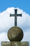 Kors av metall på ett stenjordklot, blå himmel med vita moln Arkivfoto
