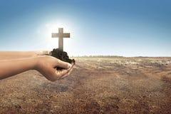 Kors med jord i människahänder på landet Royaltyfria Foton