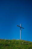 Kors på överkanten av berget i mitt av en äng Royaltyfria Bilder