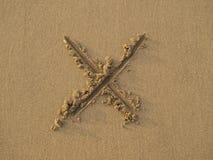 kors tecknat sandtecken arkivbilder