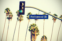 Korsa det bearbetade Hollywood tecknet och trafikljus med palmträd arkivbilder