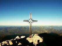 Korsa med dendyrbara stenen som lyfts på bergtoppmötet i fjällängar Maximal kor Royaltyfria Foton