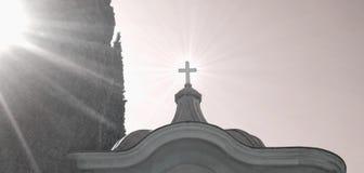 Korsa på överkanten av kapellet i kyrkogård med solstrålar fotografering för bildbyråer