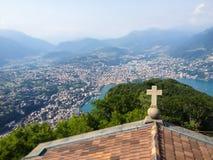 Korsa på kyrkligt tak och bästa sikt av Lugano sjön och staden från överkant av Monte San Salvatore med panorama- landskap för be arkivbilder