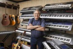 Korsade armar för Music Store ägareanseende arkivbild