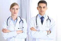 Korsade den stående raksträckan för doktorer med armar i sjukhus Läkare som är klara att hjälpa Begrepp av sjukvården, teamwork o Royaltyfria Bilder
