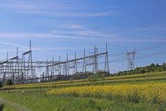 Korsar elektriska linjer för hög spänning den elektriska stationen för bergig mestnost i sommaren under den öppna himlen bunden i Arkivbild