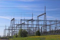 Korsar elektriska linjer för hög spänning den elektriska stationen för bergig mestnost i sommaren under den öppna himlen bunden i Royaltyfri Bild