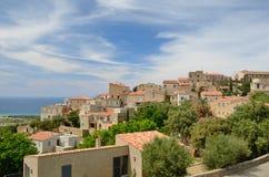 Korsikansk stad på berglutningen Arkivbild